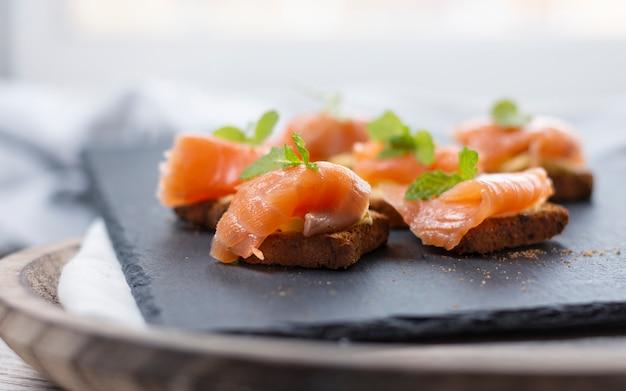Salmone affumicato su pane tostato con burro con foglia di menta su pietra nera e vecchia tavola di legno Foto Premium