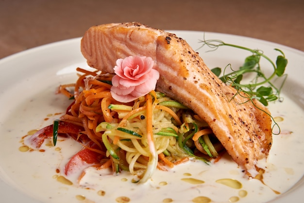 Salmone al forno con salsa di panna su uno spazio buio, verdure tritate finemente, vista dall'alto. salmone fiorentino Foto Premium