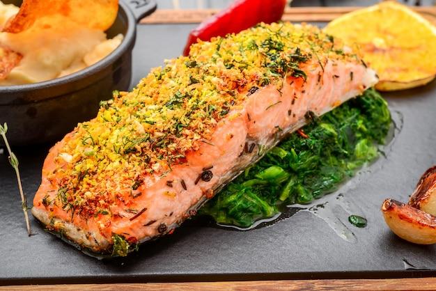 Salmone arrostito sul tagliere sulla tavola di legno Foto Premium