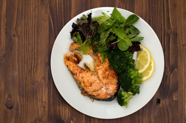 Salmone fritto con broccoli sul piatto Foto Premium