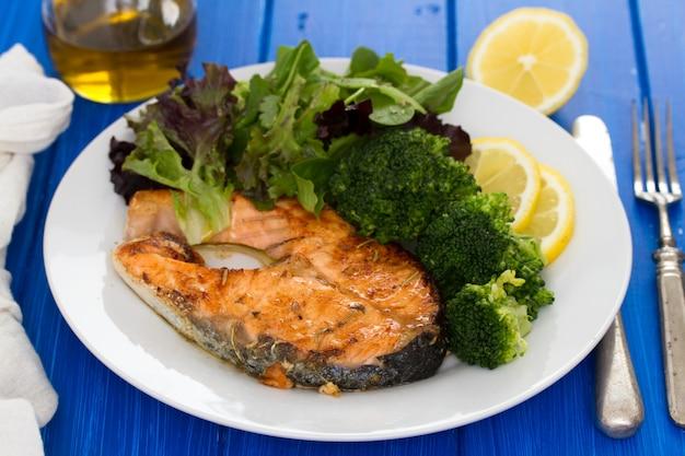 Salmone fritto sul piatto su superficie di legno Foto Premium