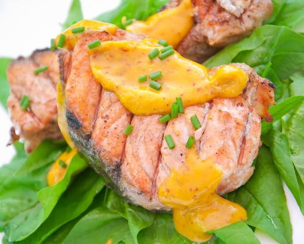 Salmone grigliato su cuscino di spinaci con salsa all'arancia e senape Foto Premium