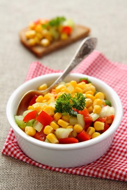 Salsa di mais fatta in casa in una ciotola bianca con cucchiaio Foto Premium