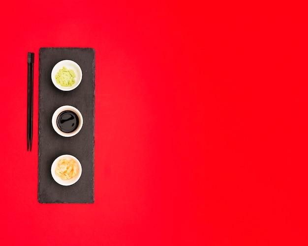 Salsa di soia; wasabi e zenzero su un piatto di pietra su sfondo rosso con spazio per il testo Foto Gratuite