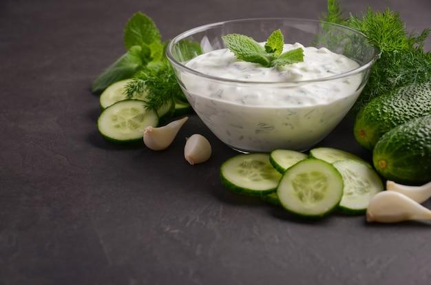 Salsa e ingredienti tzatziki. salsa di aneto e cetriolo fresco su sfondo scuro. Foto Premium