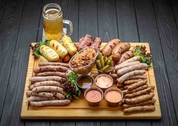 Salsicce alla griglia con un bicchiere di birra su un tavolo di legno Foto Premium