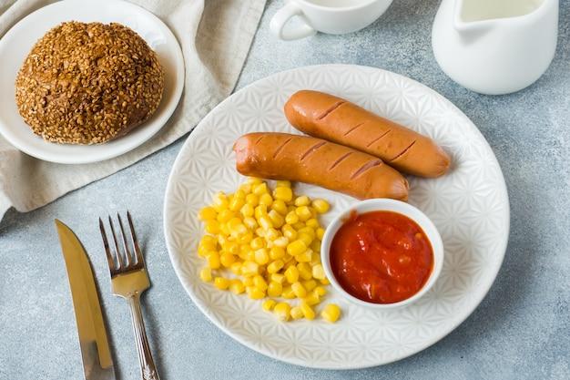 Salsicce alla griglia, mais in scatola e salsa di pomodoro su un piatto Foto Premium
