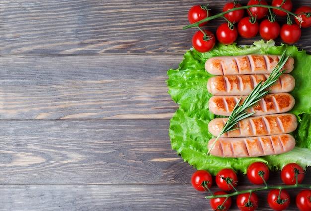 Salsicce alla griglia su foglie di lattuga verde, rosmarino, pomodorini rossi su un ramo. Foto Premium
