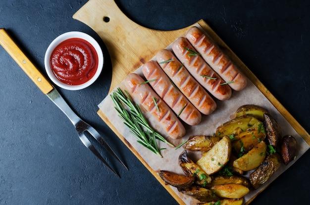 Salsicce alla griglia su un tagliere di legno. Foto Premium