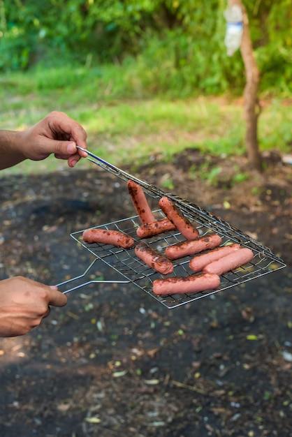Salsicce alla griglia sul fuoco. la mano dell'uomo rimuove le salsicce dalla griglia Foto Premium