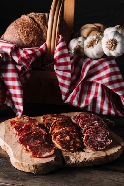 Salsicce vicino al cesto con il cibo Foto Gratuite