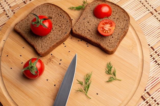 Salsiccia con pane nero e tomates sullo sfondo in legno Foto Premium