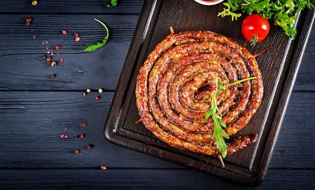 Salsiccia fatta in casa al forno su una tavola di legno. Foto Gratuite