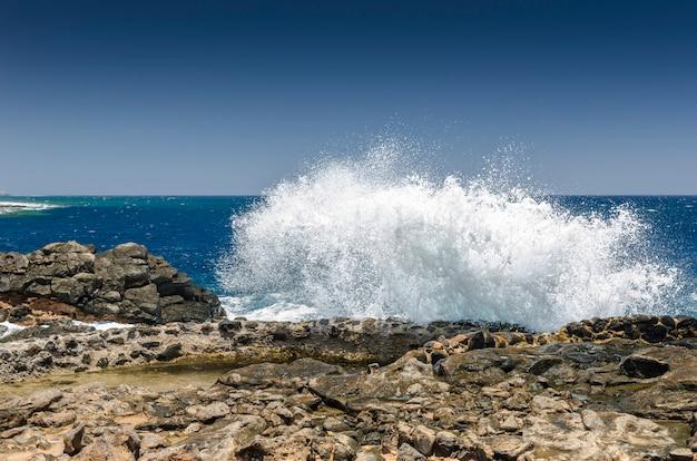Saluta per produrre sale. metodi tradizionali di produzione di sale marino a salinas del carmen, fuerteventura. produzione dall'acqua dell'oceano Foto Premium