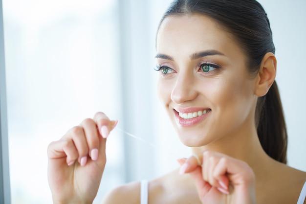 Salute dentale. donna con un bel sorriso filo interdentale denti sani. immagine Foto Premium