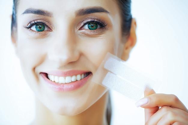 Salute e bellezza. bella ragazza con denti bianchi tenendo in mano strisce per denti che imbiancano. una donna con un bel sorriso. salute dei denti Foto Premium