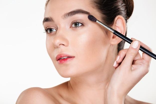 Salute e bellezza di glamour donna alla moda con i capelli scuri in panino applicando ombretto con pennello Foto Gratuite