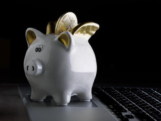 Salvadanaio con bitcoin accanto a un computer portatile. Foto Premium