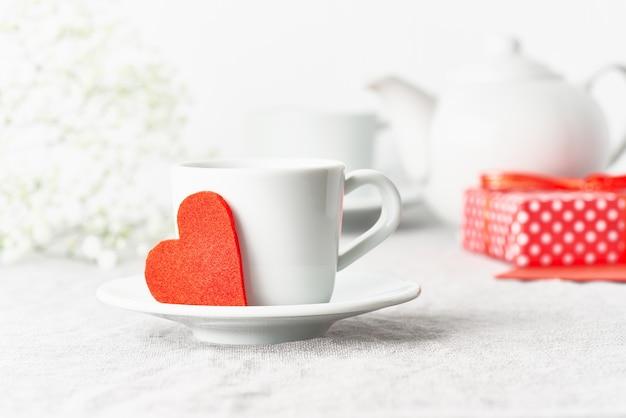 San valentino. colazione del mattino per due persone con tè, regalo, fiori. cuore di feltro rosso Foto Premium