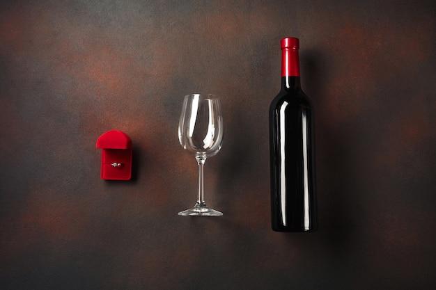 San valentino con una bottiglia di vino e un bicchiere e un anello di fidanzamento. Foto Premium