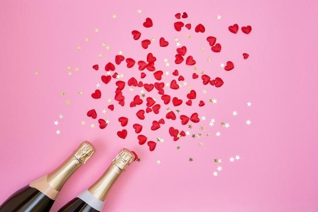 San valentino sfondo bottiglie di champagne, cuori rossi e coriandoli dorati su sfondo rosa. Foto Premium