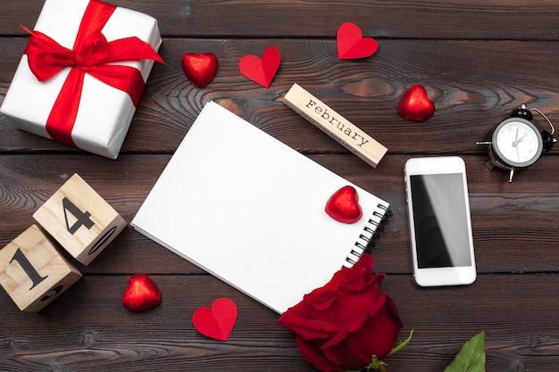 San valentino. taccuino in bianco vuoto, contenitore di regalo, fiori Foto Premium
