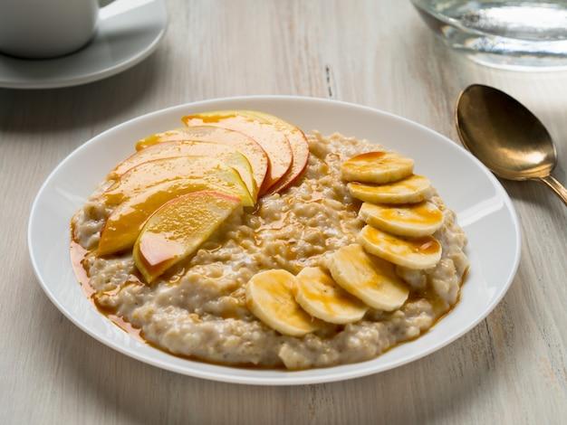 Sana colazione al mattino - farina d'avena con frutta e miele, fette di mela e bana Foto Premium