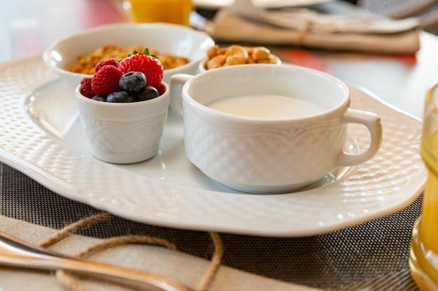 Sana colazione con succo fresco e muesli con latte e frutti di bosco Foto Premium