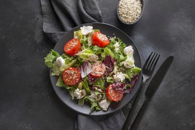Sana insalata vegana nel piatto nero con pomodoro fresco, verdure, semi di canapa per mangiare pulito. vista dall'alto. Foto Premium