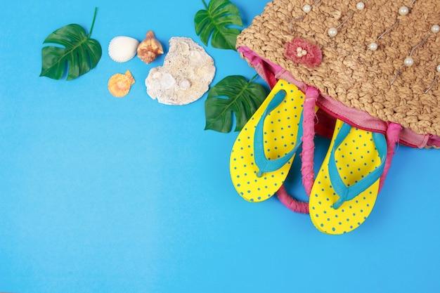 Sandali gialli in borse intrecciate su sfondo di colore blu, accessori vacanze estive Foto Premium