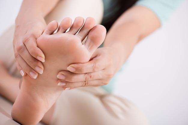 Sanità e concetto medico. donna che massaggia il suo piede doloroso Foto Premium