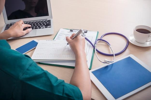 Sanità e concetto medico. medico che lavora con computer portatile, cellulare, tablet, stetoscopio, c Foto Premium