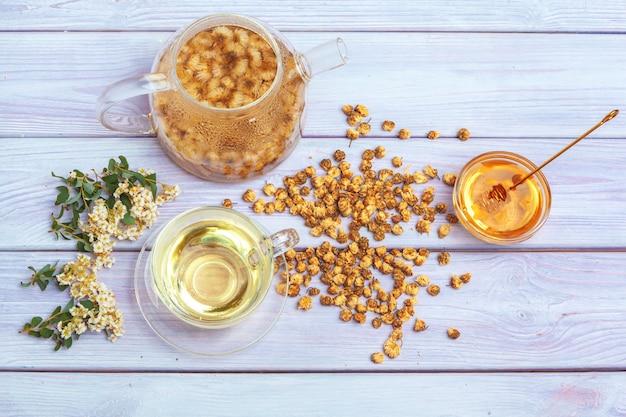 Sano camomilla in tazza di vetro. teiera, vasetto di miele Foto Premium