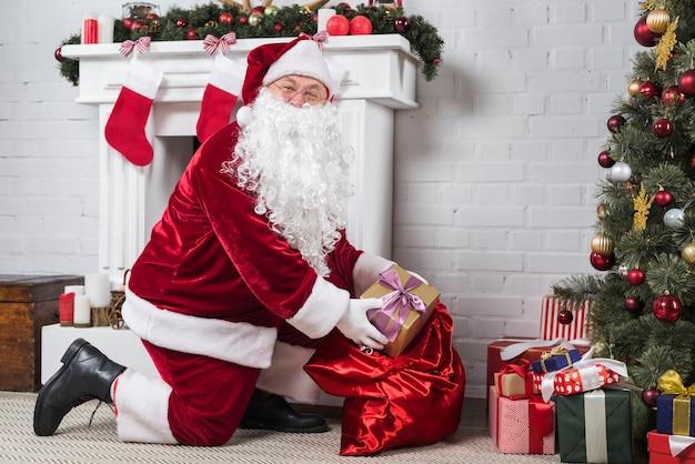 Santa mettendo regali sotto l'albero di natale decorato Foto Gratuite