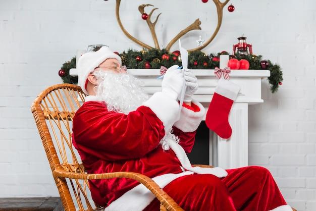 Santa seduto in sedia a dondolo con carta e penna Foto Gratuite