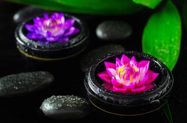 Sapone spa con acqua lilly forma di fiore su sfondo nero con pietre e gocce d'acqua Foto Premium