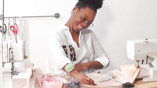 Sarta donna afro-americana, stilista che ascolta la musica tramite le cuffie mentre si lavora su tessuto nel laboratorio di studio Foto Premium