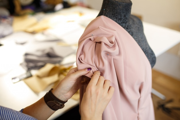 Sarta donna attaccare tessuto al manichino con aghi. creando un design elegante Foto Premium