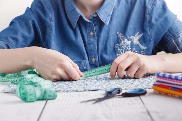 Sarta o stilista giovane donna che lavora come stilista di moda, scegli i filati per il tessuto per cucire, la professione e l'occupazione Foto Premium
