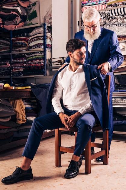 Sarto maschio che prova il cappotto blu sul suo cliente che si siede sopra la sedia di legno nel negozio Foto Gratuite