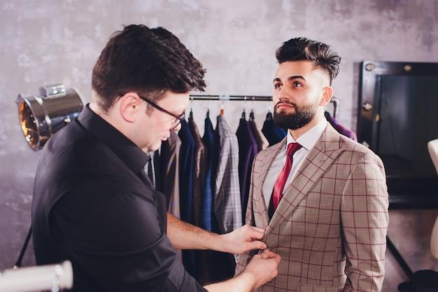 Sarto professionista che prende le misure per il vestito di cucito al negozio dei sarti Foto Premium