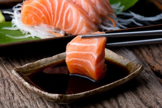 Sashimi di salmone con salsa shoyu. Foto Premium