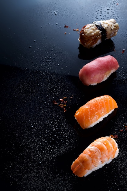 Sashimi, uramaki e nigiri con riso, salmone o tonno, gamberi in nero con gocce d'acqua Foto Premium