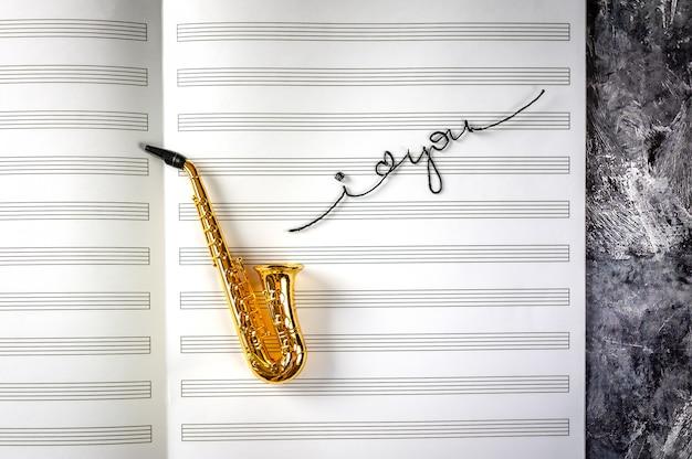 Sassofono sullo sfondo del taccuino di musica con le parole Foto Premium