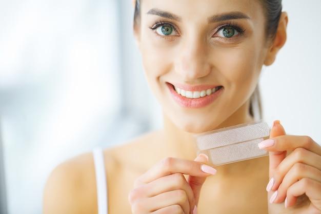 Sbiancamento dei denti. striscia d'imbiancatura della bella tenuta sorridente della donna. Foto Premium