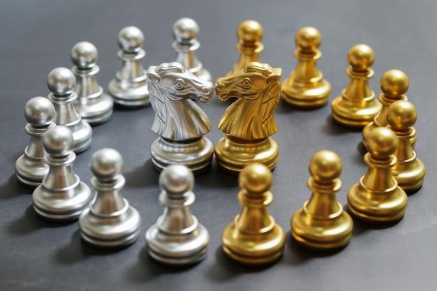 Scacchi in oro e argento su sfondo nero, concentrarsi sul cavaliere Foto Premium