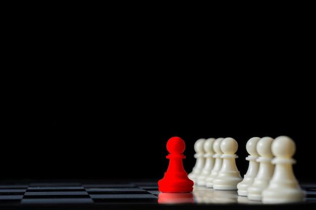 Scacchi rossi che stanno fuori dagli scacchi bianchi sulla scacchiera e sul fondo nero. concetto di leadership. Foto Premium