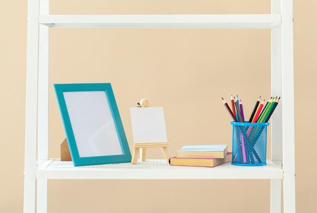 Scaffale bianco con libri e articoli di cancelleria contro la parete beige Foto Premium