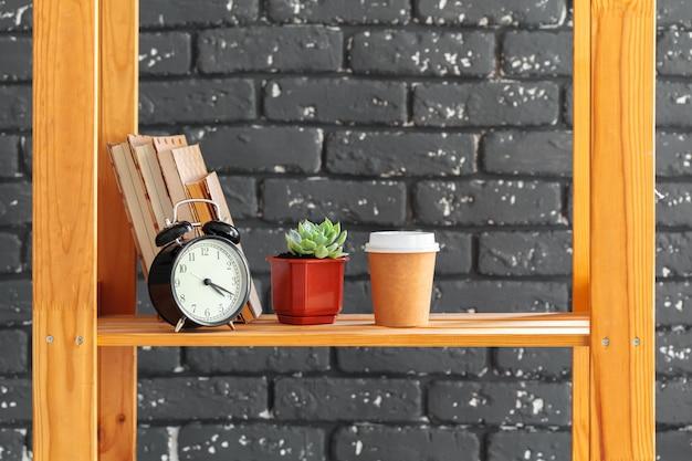 Scaffale in legno con libri e roba contro il muro di mattoni nero Foto Premium