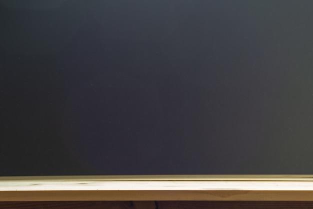 Scaffali superiori vuoti o legno della tavola sul fondo della lavagna. Foto Premium